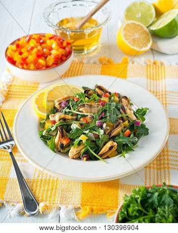 A delicious citrus honey mussel salad with arugula peppers lemon and lime.