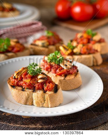 Delicious mussels bruschetta with tomato parsley olive oil and garlic on grilled french bread.