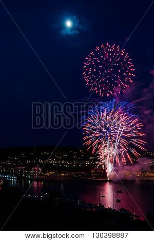 Show of fireworks at the finish of the celebration of the National Day of acceptance on the anniversary of the Norwegian Constitution - May, 17, 2016, Tonsberg, Norway Can see on picture city by night with port on the Oslofjord port with buildings port.