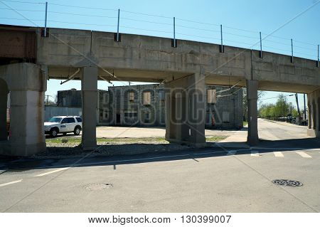 JOLIET, ILLINOIS / UNITED STATES - APRIL 26, 2015: An abandoned building is seen between the support columns of a railroad bridge in downtown Joliet.
