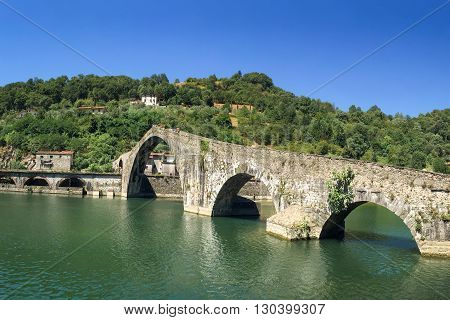 Unique Old Stone Bridge - the medieval Ponte Maddalena or Devils Bridge in Tuscany. Unrecognizable people at the crest of the bridge are included for scale.