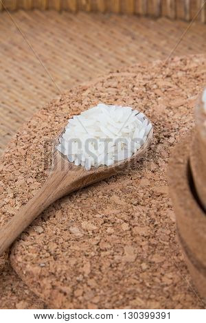 Raw and uncooked rice in wooden spoon,shallow Depth of Field,Focus on rice.