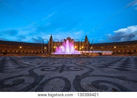 The spectacular and illuminated Square of Spain in Spanish Plaza de Espana, after sunset with its famous fountain and central building, Seville, Andalucia, Spain.