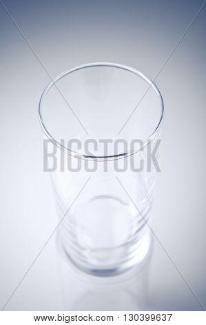 Empty glass on gradient grey blue background