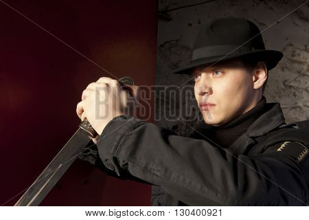 A dangerous man holding dagger on dark background