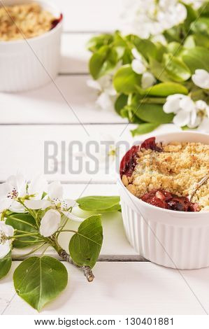 Crumble with strawberry and black currant on a white wooden background with flowering branches of apple trees