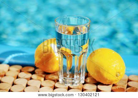 Fresh water and lemons near swimming pool