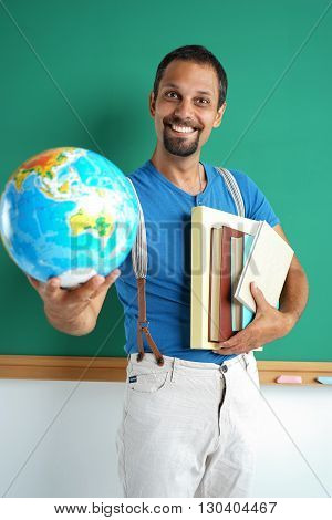 Geography teacher showing globe. Photo adult man with books and globe creative concept with Back to school theme