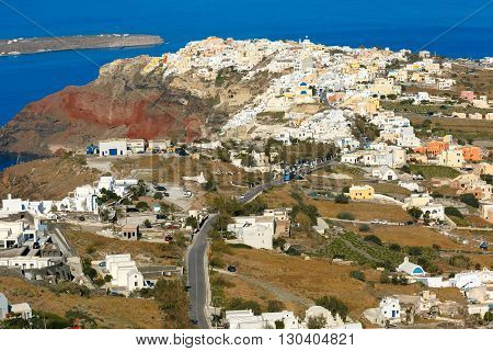 Aerial view of Oia or Ia and Finikia on the island Santorini, white houses, windmills and church with blue domes, Greece
