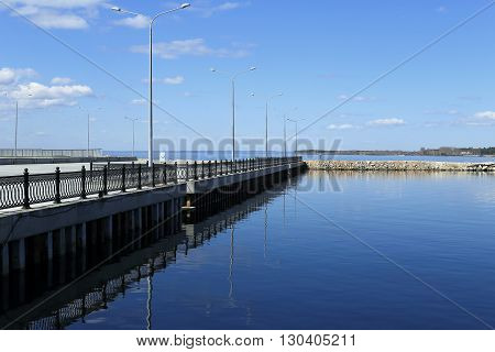 empty pier and calm water on a background of blue sky and clouds. beautiful fencing and pillars.
