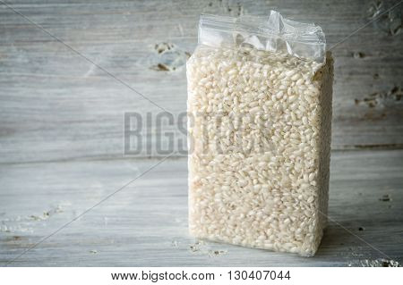 Packaging with Arborio rice on wooden boards horizontal