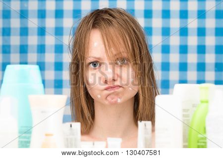 Young white-skinned girl with wet hair without makeup is in disbelief in front of cosmetic products. Skincare and beauty concept. Frontal portrait