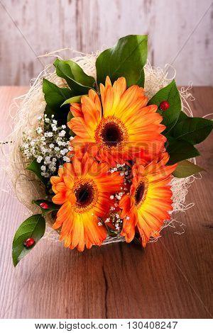 Bouquet Of Orange Gerberas On Wooden Board