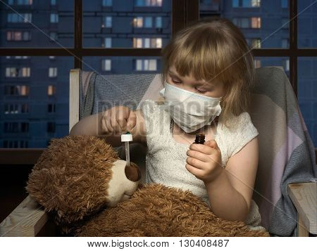 Little girl in medical mask dripping drops a toy bear. The house, in the evening, the windows of houses, the city. Conceptually about diseases, infections and allergies
