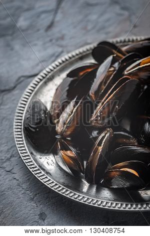 Folds mussels on an old metal plate on a slate horizontal