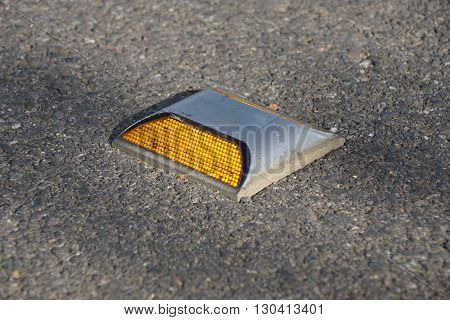 Metal Road Stud With Yellow Reflector On Asphalt Road