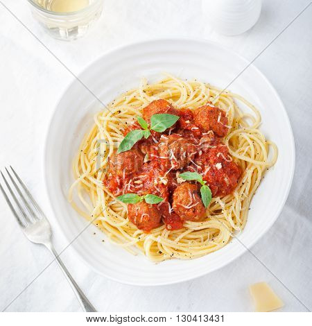 Meatballs in tomato sauce and fresh basil with spaghetti on a white background Top view
