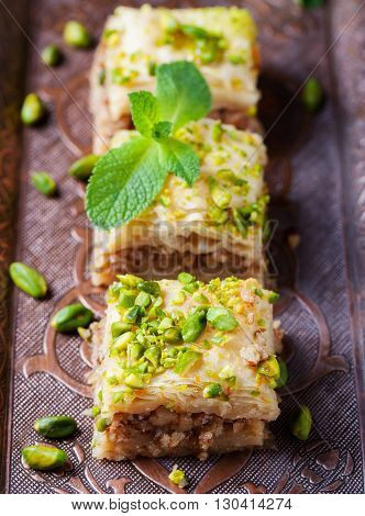 Baklava with pistachio Turkish pastry dessert on a authentic cooper tray