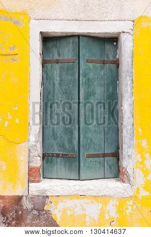 Picturesque old window with green shutters on yellow wall (Burano island Venice Italy)