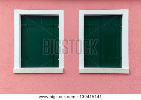 Picturesque two old windows with dark green shutters on light pink wall (Burano island Venice Italy)