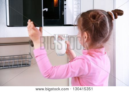 Little girl using a microwave oven