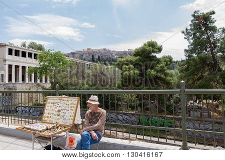Athens Greece - April 30 2016: Street vendor selling jewellery near Stoa of Attalos of the Ancient Agora of Athens with the Acropolis in the background.