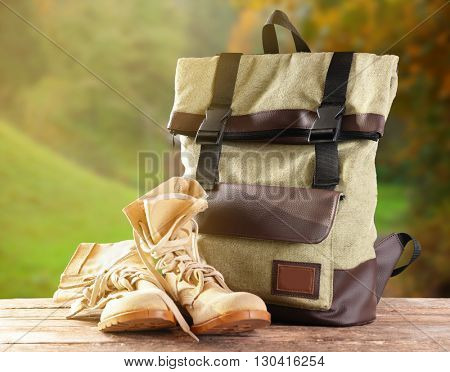 Tourism concept. Backpack and pair of boots on blurred nature background
