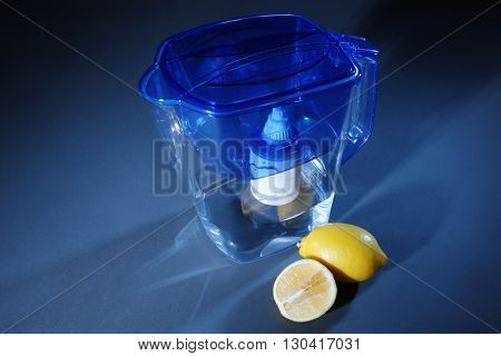 Water filter jug and lemons on dark background