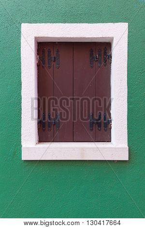 Picturesque old window with brown shutters on green wall (Burano island Venice Italy)