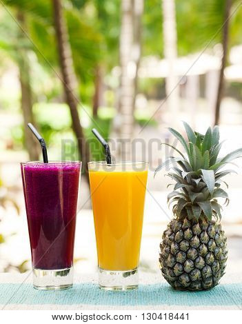 Glass of pineapple and dragon fruit smoothie, juice and fresh fruit on a outdoor tropical background