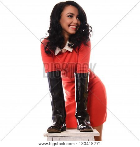 Young slim woman in red dress and brown boots on white background.