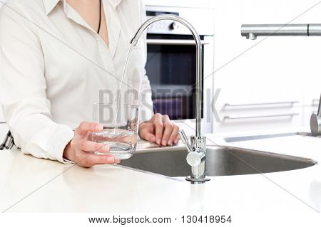 Woman pours fresh clean water into the glass