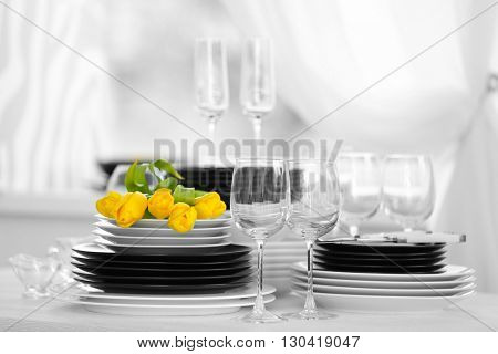 Set of dishes with yellow tulips for dinner party