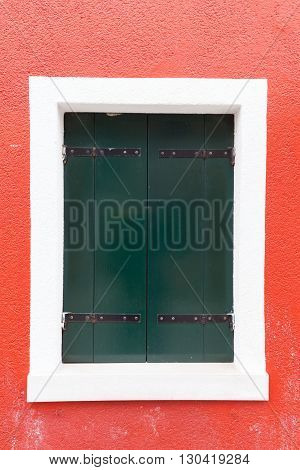 Picturesque old window with dark green shutters on red wall (Burano island Venice Italy)