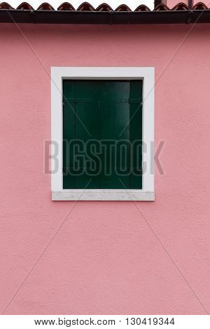 Picturesque window with dark green shutters on light pink wall (Burano island Venice Italy)