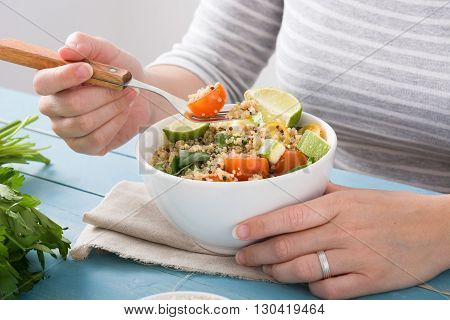 Woman eating quinoa salad in white bowl