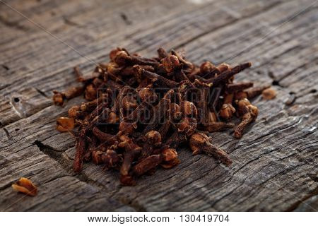 A heap of cloves, on wooden surface.