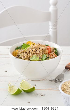 Quinoa salad in bowl, tomatoes and spinach