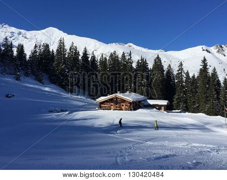 Winter in Austria in the mountains - skiers and hut