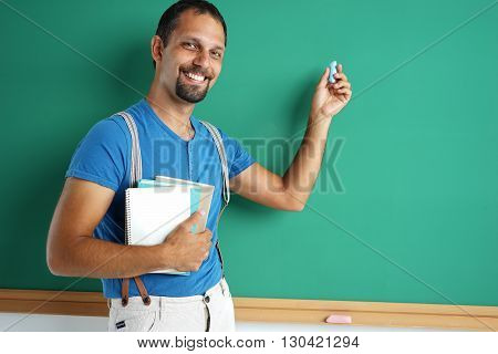 Exemplary student standing near blackboard with books and chalk. Photos adult student education concept