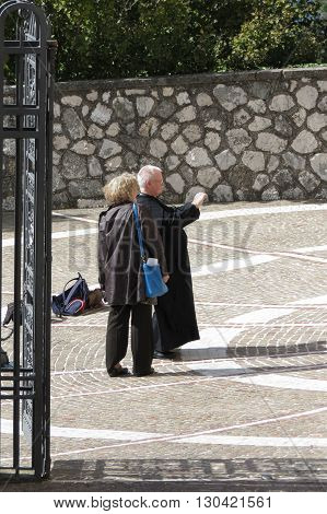 MONTECASSINO ITALY - CIRCA OCTOBER 2015: unidentified senior priest taking a picture with a digital camera
