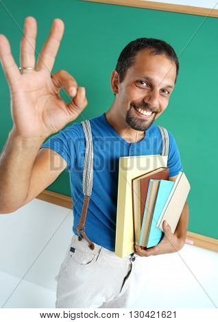 Happy smiling man showing okay gesture. Photo of smiling adult student creative concept with Back to school theme