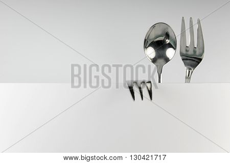 Metal spoon and two forks formed into conceptual fantasy figure