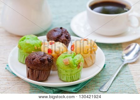 Assortment of muffins vanilla, chocolate, pandan on a white plate. Outdoor tropical background