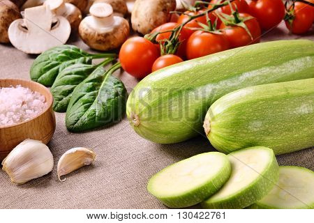 Two whole zucchini and a few sliced pieces, cherry tomatoes, mushrooms, salt in wooden salt shaker, cloves of garlic and spinach leaves on a linen cloth.