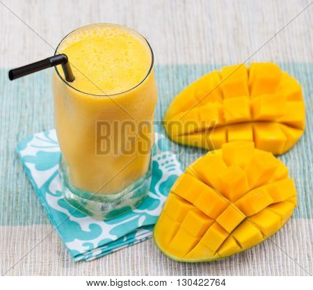Fresh tropical fruit smoothie mango juice and fresh mango on a outdoor tropical background Copy space