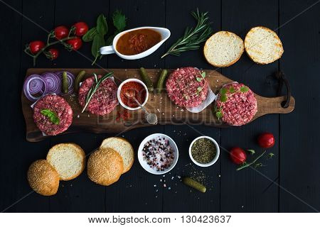Ingredients for cooking burgers. Raw ground beef meat cutlets on wooden chopping board, red onion, cherry tomatoes, greens, pickles, tomato sauce, cheese, herbs and spices over black background, top view, horizontal