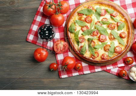 Pizza Margherita with arugula and vegetables on wooden table