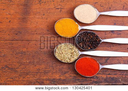 Aromatic spices on five spoons. Food background .