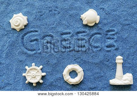 Greece written on the sand blue with summer symbol